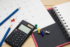 Τοπ σημειωματάριο, υπολογιστής, μολύβι και ημερολόγιο άποψης που τίθενται σε ξύλινο Στοκ εικόνες με δικαίωμα ελεύθερης χρήσης