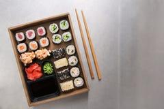 Τοπ σύνολο άποψης maki και ρόλων σουσιών με το chopstics, το ρύζι, τη σόγια, το wasabi και την πιπερόριζα στο γκρίζο υπόβαθρο Στοκ φωτογραφίες με δικαίωμα ελεύθερης χρήσης