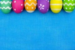 Τοπ σύνορα αυγών Πάσχας πέρα από το μπλε burlap υπόβαθρο Στοκ Φωτογραφίες