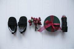 Τοπ σύνολο δώρων στο άσπρο ξύλινο υπόβαθρο , Παιχνίδια, παπούτσια μωρών, τραίνο παιχνιδιών, μούρα που οργανώνονται με το διάστημα Στοκ Εικόνα