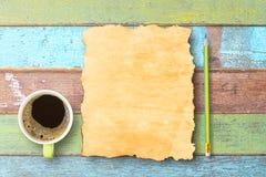 Τοπ φλυτζάνι καφέ άποψης, μολύβι και παλαιό έγγραφο για τον ξύλινο πίνακα γραφείων στοκ εικόνες
