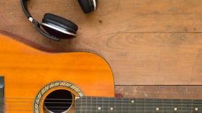 Τοπ χώρος εργασίας άποψης με το ακουστικό και ακουστική κιθάρα σε ξύλινο Στοκ Εικόνα