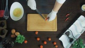 Τοπ όψη Αρχιμάγειρας που τεμαχίζει ένα καρότο με το κόκκινο πιπέρι στον τέμνοντα πίνακα Αφαιρέστε τους σπόρους απόθεμα βίντεο