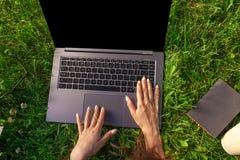 Τοπ όψη Γυναίκα που εργάζεται στον υπολογιστή PC lap-top με την κενή μαύρη κενή οθόνη στο διάστημα αντιγράφων στο πάρκο στην πράσ Στοκ φωτογραφία με δικαίωμα ελεύθερης χρήσης
