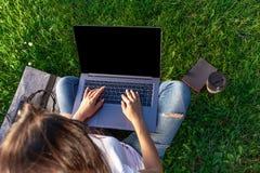 Τοπ όψη Γυναίκα που εργάζεται στον υπολογιστή PC lap-top με την κενή μαύρη κενή οθόνη στο διάστημα αντιγράφων στο πάρκο στην πράσ Στοκ φωτογραφίες με δικαίωμα ελεύθερης χρήσης