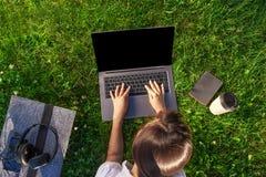Τοπ όψη Γυναίκα που εργάζεται στον υπολογιστή PC lap-top με την κενή μαύρη κενή οθόνη στο διάστημα αντιγράφων στο πάρκο στην πράσ Στοκ Εικόνες