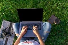 Τοπ όψη Γυναίκα που εργάζεται στον υπολογιστή PC lap-top με την κενή μαύρη κενή οθόνη στο διάστημα αντιγράφων στο πάρκο στην πράσ Στοκ Φωτογραφίες