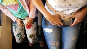 Τοπ όψη Κλείστε επάνω των χεριών θηλυκών και παιδιών που στερεώνουν, πόρπη επάνω η ζώνη ασφαλείας καμπινών καθμένος στο κάθισμα α απόθεμα βίντεο