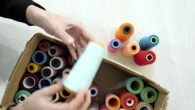 Τοπ όψη Τα χέρια παίρνουν τα πολύχρωμα spolls από το κιβώτιο απόθεμα βίντεο