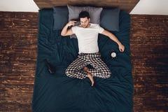 Τοπ όψη Το ενήλικο άτομο βρίσκεται στο κρεβάτι δίπλα στο ξυπνητήρι και το μπουκάλι του κρασιού, που συνδέει το πυροβόλο όπλο με τ στοκ εικόνα
