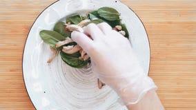 Τοπ όψη Clouse επάνω στα τρόφιμα Ο αρχιμάγειρας βάζει τη σαλάτα σε ένα άσπρο πιάτο Η σαλάτα από το σπανάκι, κοτόπουλο, αυγά κυνήγ απόθεμα βίντεο