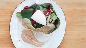 Τοπ όψη Clouse επάνω στα τρόφιμα Ο αρχιμάγειρας κάνει τη σαλάτα σε ένα άσπρο πιάτο Η σαλάτα από το σπανάκι, κοτόπουλο, αυγά κυνήγ φιλμ μικρού μήκους