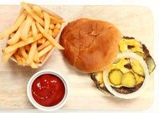 Τοπ Burger και τηγανητά άποψης στον τέμνοντα πίνακα Στοκ Φωτογραφίες