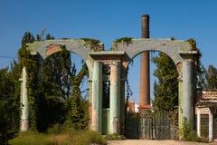 Τουβλότοιχοι ενός παλαιού εγκαταλειμμένου εργοστασίου με μια καπνοδόχο Ένα εγκαταλειμμένο εργοστάσιο με έναν υψηλό σωλήνα τούβλου στοκ εικόνα