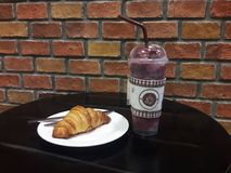 Τουβλότοιχος και ποτό και ένας croissant στον πίνακα στοκ εικόνες