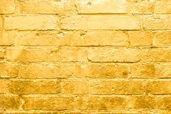 Τουβλότοιχος που χρωματίζεται στο χρυσό, χρυσό υπόβαθρο γκράφιτι Στοκ Φωτογραφίες