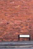 Τουβλότοιχος με το πεζοδρόμιο και σημάδι στο μέτωπο στοκ φωτογραφία με δικαίωμα ελεύθερης χρήσης