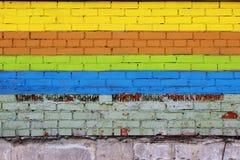 τουβλότοιχος που χρωματίζεται με τις χρωματισμένες χρωστικές ουσίες υπό μορφή λωρίδων: κίτρινος, καφετής, πράσινος και μπλε Στοκ φωτογραφίες με δικαίωμα ελεύθερης χρήσης