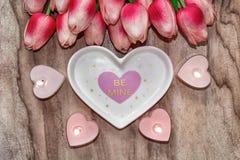Τουλίπες λουλουδιών, ένα καρδιά-διαμορφωμένο πιάτο και ένα καρδιά-διαμορφωμένο κερί Εορταστικό υπόβαθρο στην ημέρα του βαλεντίνου στοκ φωτογραφία