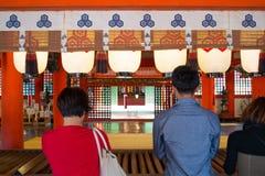Τουρίστας για να δει την επιπλέουσα πύλη torii και να προσεηθεί το προνόμιο στη λάρνακα Itsukushima στοκ εικόνες