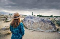 Τουρίστας γυναικών κοντά στην αρχαία ζωγραφική πετρών στοκ εικόνες