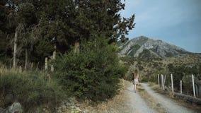 Τουρίστας γυναικών με ένα περπάτημα καμερών Όμορφη άποψη των ασπρισμένων σπιτιών Ο νέος θηλυκός φωτογράφος φορά το ψαθάκι φιλμ μικρού μήκους
