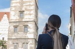 Τουρίστας γυναικών με την τηλεφωνική κάμερα της στα χέρια που πυροβολεί στην Πράγα Στοκ φωτογραφία με δικαίωμα ελεύθερης χρήσης