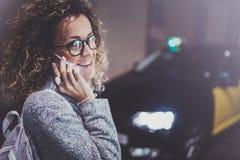 Τουρίστας γυναικών που φορά τα γυαλιά ματιών που καλούν την υπηρεσία ταξί με τηλέφωνο κυττάρων, ενώ στέκεται στην οδό στη νύχτα Στοκ φωτογραφίες με δικαίωμα ελεύθερης χρήσης
