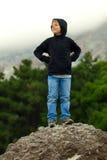 Τουρίστας εφήβων αγοριών που στέκεται σε έναν βράχο και ένα χαμόγελο Στοκ Εικόνες