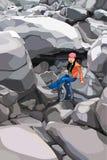 Τουρίστας κοριτσιών κινούμενων σχεδίων με ένα σακίδιο πλάτης στους βράχους Στοκ Φωτογραφίες