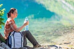 Τουρίστας κοριτσιών με ένα μπουκάλι νερό που θαυμάζει ένα όμορφο mountai Στοκ Εικόνες
