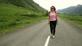 Τουρίστας κοριτσιών με το σακίδιο πλάτης που περπατά στο δρόμο μεταξύ των βουνών ο νέος τουρίστας γυναικών ταξιδεύει φιλμ μικρού μήκους