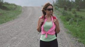 Τουρίστας κοριτσιών με το σακίδιο πλάτης που περπατά στο δρόμο μεταξύ των βουνών ο νέος τουρίστας γυναικών ταξιδεύει απόθεμα βίντεο