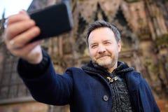 Τουρίστας Μεσαίωνα που κάνει selfie την κινητή φωτογραφία με διάσημο; η athedral Notre Dame του Στρασβούργου στο υπόβαθρο Στοκ εικόνες με δικαίωμα ελεύθερης χρήσης