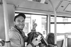 Τουρίστας με έναν πλοηγό σακιδίων πλάτης και τηλεφώνων στο λεωφορείο Στοκ Φωτογραφίες