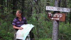 Τουρίστας με έναν χάρτη κοντά στα σημάδια Χωριό Tungur επιγραφών, βουνό της Kara Turek απόθεμα βίντεο