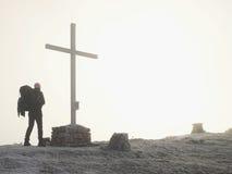 Τουρίστας με τη μεγάλη στάση σακιδίων πλάτης στο διαγώνιο μνημείο στην αιχμή βουνών Το άτομο προσέχει στο misty αλπικό φυσητήρα κ Στοκ Φωτογραφίες
