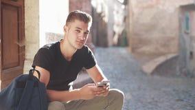 Τουρίστας με τη συνεδρίαση σακιδίων πλάτης στα σκαλοπάτια εισόδων και τη χρησιμοποίηση του κινητού τηλεφώνου Νέο ελκυστικό άτομο  απόθεμα βίντεο