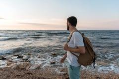 Τουρίστας με το σακίδιο πλάτης που στέκεται στο υπόβαθρο της θάλασσας στοκ εικόνα