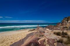Τουρίστας με backpacks σε μια μεγάλη πέτρα και την απόλαυση της θέας θάλασσας. Εθνικό πάρκο του Ben Boyd, Αυστραλία Στοκ Εικόνες