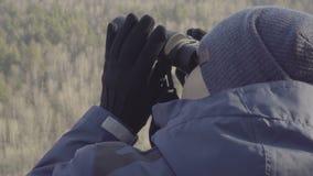 Τουρίστας οδοιπόρων νεαρών άνδρων άποψης κινηματογραφήσεων σε πρώτο πλάνο που κοιτάζει με διοφθαλμικό στην κορυφή του βράχου φιλμ μικρού μήκους