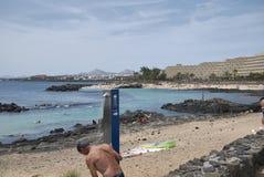 Τουρίστας που έχει ένα ντους Arrecife στην παραλία Στοκ φωτογραφίες με δικαίωμα ελεύθερης χρήσης