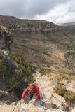 Τουρίστας που αναρριχείται στον απότομο βράχο στο χρυσό εθνικό πάρκο Χάιλαντς πυλών, Νότια Αφρική Περιπέτεια και εξερεύνηση στην  Στοκ εικόνες με δικαίωμα ελεύθερης χρήσης