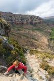 Τουρίστας που αναρριχείται στον απότομο βράχο στο χρυσό εθνικό πάρκο Χάιλαντς πυλών, Νότια Αφρική Περιπέτεια και εξερεύνηση στην  Στοκ Εικόνα