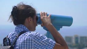 Τουρίστας που εξετάζει μέσω των διοπτρών το Sochi Νέα γυναίκα με το σακίδιο πλάτης που κοιτάζει μέσω των διοπτρών από έναν πύργο  φιλμ μικρού μήκους