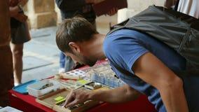 Τουρίστας που εξετάζει μέσω των νομισμάτων στο ξύλινο κιβώτιο στον πίνακα την αγορά οδών, ταξίδι φιλμ μικρού μήκους
