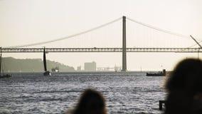 Τουρίστας που εξετάζει τη γέφυρα και τα σκάφη στο ανάχωμα στη Λισσαβών φιλμ μικρού μήκους