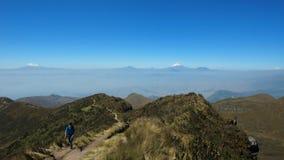 Τουρίστας που περπατά προς το Rucu Pichincha κοντά στην πόλη του Κουίτο με το ηφαίστειο Cotopaxi και Antisana στο υπόβαθρο Στοκ Φωτογραφία