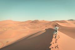 Τουρίστας που περπατά στους φυσικούς αμμόλοφους Sossusvlei, έρημος Namib, εθνικό πάρκο Namib Naukluft, Ναμίμπια Φως απογεύματος ρ Στοκ Φωτογραφία