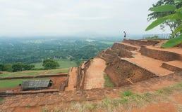 Τουρίστας που προσέχει το φυσικό τοπίο με την αρχαία λίμνη της πόλης Sigiriya, των καταστροφών και της archeological περιοχής στη Στοκ εικόνες με δικαίωμα ελεύθερης χρήσης